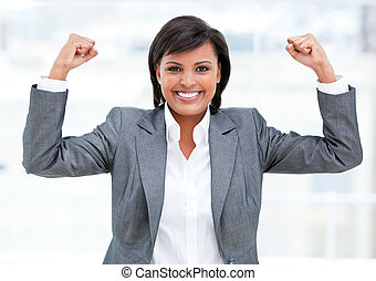 Very positive business woman showing her muscles