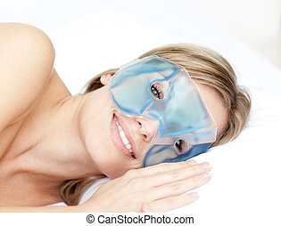Cute women with an eye gel mask on bed