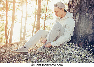 Young man tying shoelaces outdoor - Sporty young man tying...