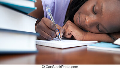 Close-up of a tired afro-american teen girl studying in a...