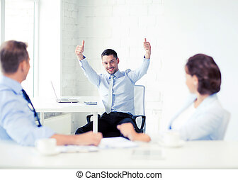 happy businessman showing thumbs up in office - picture of...