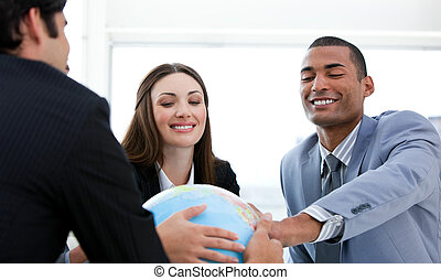 Successful business people having a meeting around a terrestrial globe in a company
