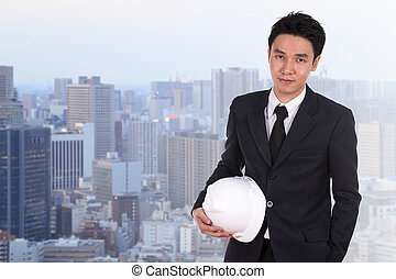 engineer holding white helmet with city background