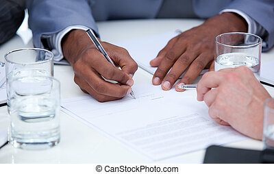 Close-up of ambitious business people closing a deal in a...