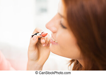 close up of hand applying lipstick to woman lips - beauty,...