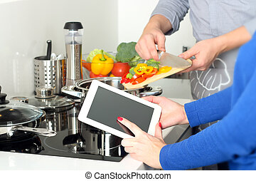 cooking, technology and home concept - closeup of woman...