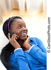 Afro-american woman on phone lying on a sofa in the...