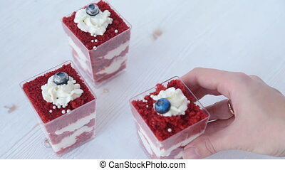 Layered dessert with fruits, nuts and cream cheese in glass jar