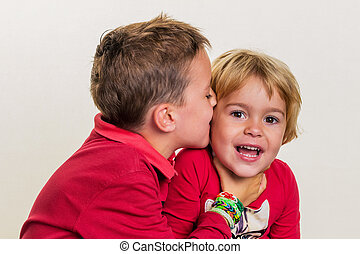 siblings have fun - sisters whisper to each other a secret...