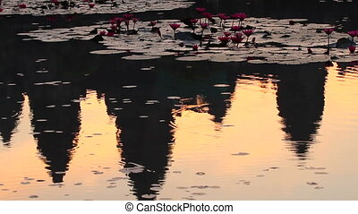 Sunrise in Angkor Wat, a temple complex in Cambodia and the largest religious monument in the world. Reflection in pond with lotuses. UNESCO World Heritage Site.