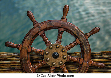 Ships Wheel Against Ocean Water - Nautical Detail Of A...