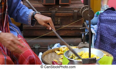 Woman boils silkworm cocoons and makes a silk thread....