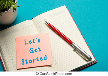 Job interview concept . Office table top view. Notepad, pen and reminder with word Let's Get Started