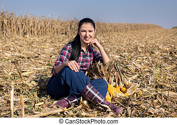 Woman in corn field - Young smiling girl sitting on...