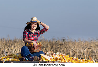 Woman sitting on corn pile - Young happy woman with straw...