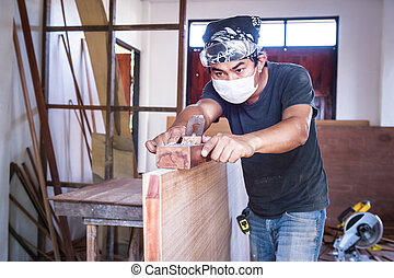 carpenter man take a planer tool with wood in workshop