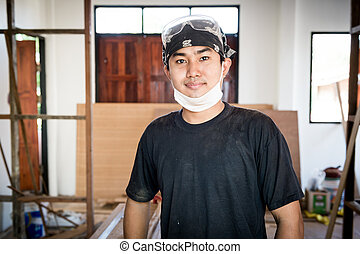 Young male carpenter portrait in workshop interior