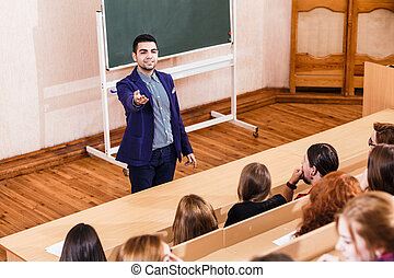 Teacher explaining something to students - Young teacher...