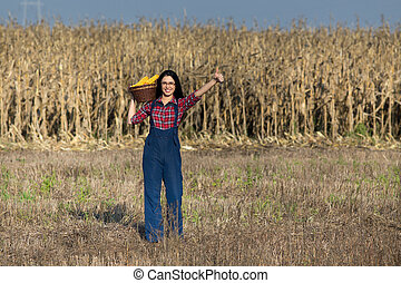 Woman in corn field - Young happy girl holding basket with...