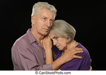 Sad elderly couple on a black background