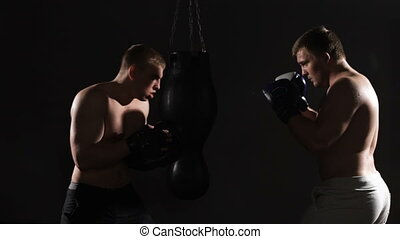 Two boxing men exercising together at the health club