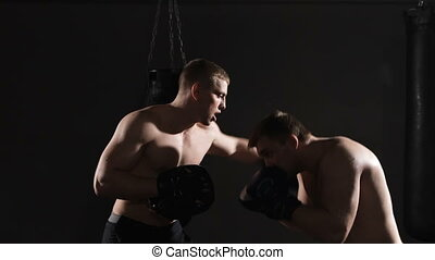Two boxing men exercising together at the health club Dark...