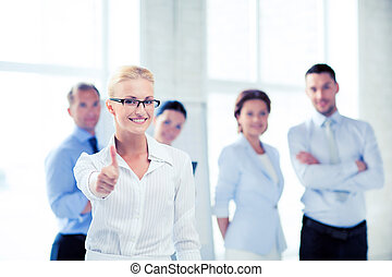 businesswoman in office showign thumbs up - attractive...