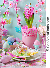 easter table decoration with eggs and flowers in pastel...