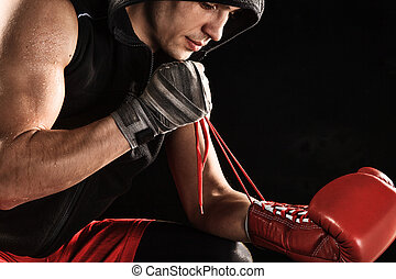 The young man kickboxing lacing glove - The young male...
