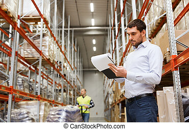 businessman writing to clipboard at warehouse - wholesale,...
