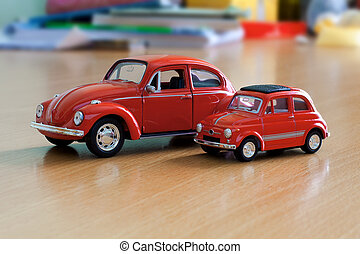 Two red toy cars on table