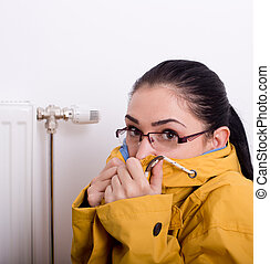 Woman freezing next to radiator - Young woman in yellow...