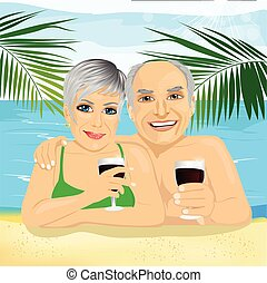 lovely senior couple drinking red wine lying on the beach