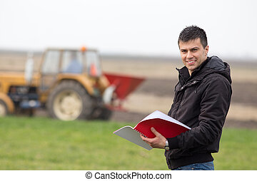 Satisfied farmer in the field - Young landowner with...