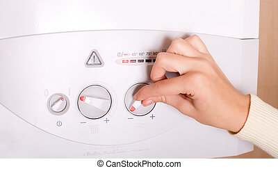 Hand on gas boiler - Close up of female hand turning on gas...