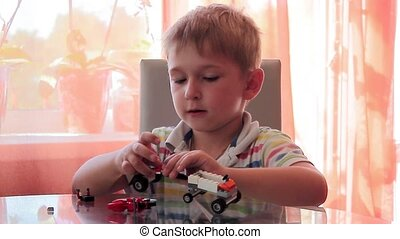boy design machine from colored toy pieces on his table