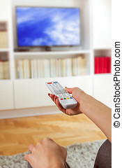 Changing Channel on TV - Television remote control in woman...