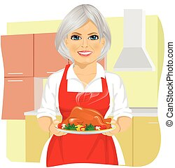 Sweet grandmother in red apron cooking traditional...
