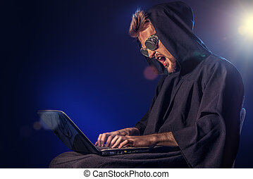 dangerous man - A hacker hiding his face behind glasses and...