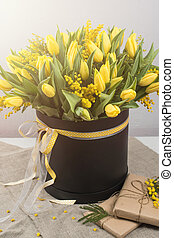 Bright spring bouquet of tulips and mimosa flowers Mothers...
