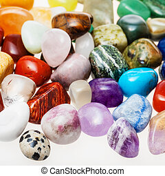many tumbled natural mineral gemstones close up on white