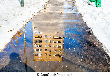 reflection of house in puddle on footpath - reflection of...