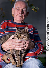 Old man with cat - Old man holding tabby cat in the lap in...