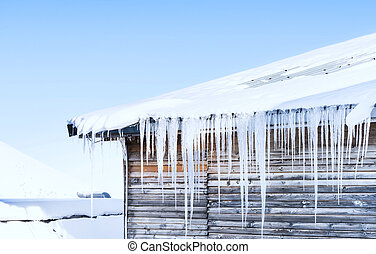 long icicles hanging from the roof of the house