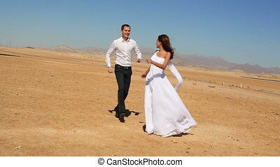 Groom holds in hands his beautiful bride. Sunny beach background. Honeymoon