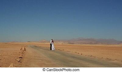 Happy young wedding couple softly hugs in the desert. Honeymoon in Egypt
