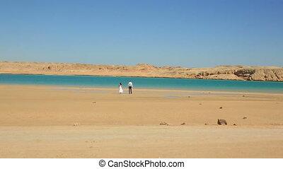 Wedding couple walks on the beach in Egypt. Exotic honeymoon...