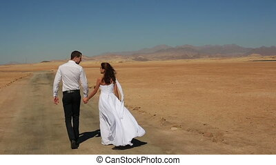 Happy young wedding couple walks and holding hands in the desert. Honeymoon in Egypt