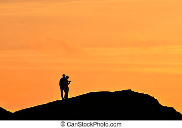 Couple Silhoutted with warm orange light at sunset -...