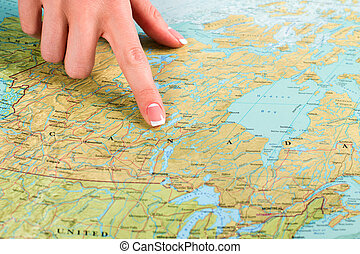 Map of Canada in atlas Female finger points at Canada Just...